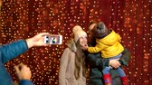 Father taking photo of family at Christmas market on the night.