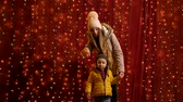 Two teenager posing and waving in front of lights wall at Christmas market. Stock Footage
