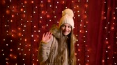 Cute teenager posing and waving in front of lights wall at Christmas market.