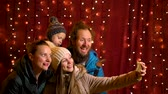 Daughter taking selfie with family at Christmas market.