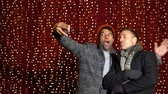 Two friends taking selfie in front of light wall at Christmas market.