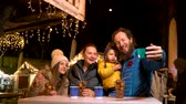 Father taking selfie with family at traditional Christmas market in Zagreb, Croatia. Stock Footage