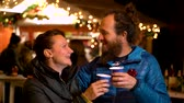 Couple enjoying traditional drink at Christmas market, Zagreb, Croatia.