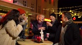 Group of friends laughing and cheering with traditional drink at Christmas market, Zagreb, Croatia.