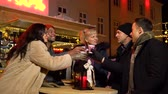 mulled : Group of friends laughing and cheering with traditional drink at Christmas market, Zagreb, Croatia.