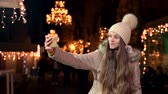 Beautiful teenager with long hair taking a selfie at Christmas market. Stock Footage