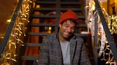 Portrait of african american man sitting on stairs at Christmas market, Zagreb, Croatia. Stock Footage