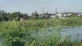 Sailing along large river Nile in Egypt through rural landscape with industrial sugar cane factory causing pollution