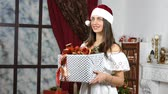 box : smiling woman in white dress and red hat with gift box