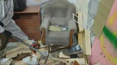 helma : APR 04, 2018 MOSCOW, RUSSIA: The man destroys an old chair by a sledgehammer in the ruins of an apartment Dostupné videozáznamy