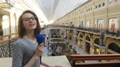říci : APR 15, 2018 MOSCOW, RUSSIA: Woman Journalist And Tv Presenter Speaks Into A Microphone in Moscow State Universal shop.