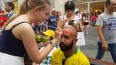 brazílie : JUN 16, 2018, MOSCOW, RUSSIA: Girls draw Croatian flags on Brazilian soccer fan face. FIFA World Cup 2018 Dostupné videozáznamy