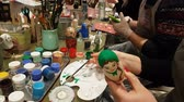 Group of people paints dolls, traditional Russian wooden toys. DEC 18, 2018 MOSCOW, RUSSIA Stock mozgókép