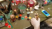 Group of people paints dolls, traditional Russian wooden toys. DEC 18, 2018 MOSCOW, RUSSIA Стоковые видеозаписи