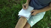 若々しい : A teenager is reading a book sitting on the grass near a tree. Blue tank top and pigeon shorts. Dark hair.