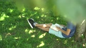 若々しい : A teenager is reading a book sitting on the grass near a tree. Blue tank top and pigeon shorts. Dark hair. Exam preparation 動画素材