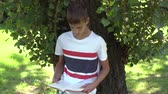 若々しい : A teenager is reading a book standing near a tree. Multi-colored T-shirt and shorts. Exam preparation 動画素材