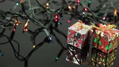 box : slider shot of christmas lights string and gift box laying on black reflective background