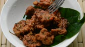 çili : fried fish patty Thai called Tod Mun on wild betel leaf bush stabbing by fork Stok Video
