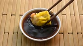 soja : steamed Chinese pork dumpling pick by wooden chopsticks and dipping soy sauce on cup