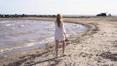 Blond girl in a white dress walking along the shoreline