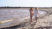 Two girls holding hands walking along the coastline, smiling and laughing