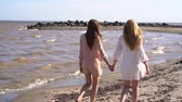 Two girls smiling and laughing, holding hands walking along the coastline Dostupné videozáznamy
