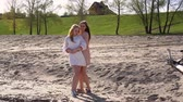 One girl hugged another on the beach, they are smiling, against the backdrop of trees and a house on a hill Dostupné videozáznamy