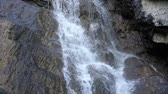 белый : Waterfall close up, the water falls and flows through the rocks