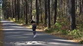 Girl athlete runs along the road in the woods. Slow motion video.
