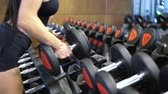 бодибилдинг : Athlete woman takes dumbbells from the rack in the gym. Hands close up. Стоковые видеозаписи