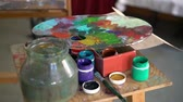 workshops : Paints, brushes and a palette are on the table close-up. Stock Footage