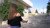 gonfiare : The girl makes the bottom of the stairs. Handheld slow motion video.