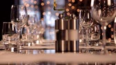 tumblers : Closeup shot of restaurant table set for dinner. Camera focus transitions from glassware on the background to salt and pepper mills on the foreground.