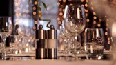 tumblers : Closeup shot of restaurant table set for many persons. Camera focus transitions from glassware on the background to wine glass and tumbler on the foreground. Stock Footage