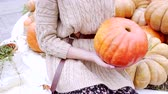 Young woman hanging pumpkin for jack olantern
