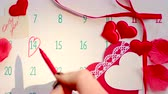 Woman hand marking February 14 on calendar page