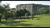 дома : View of the city from the green park hill at warm sunlight day eith buildings trees and flowers Стоковые видеозаписи