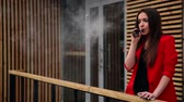 замена : spectacular young brunette outside uses fashionable and healthy e-cigarette Стоковые видеозаписи