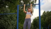 健身 : young athletic fitness woman working out at outdoor gym doing pull ups at sunrise