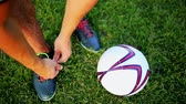 tkanička : Professional football player at practice tying laces in the boots. Close-up with the ball.