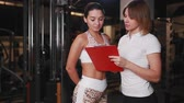 Female personal trainer talking to a woman client in a gym using a tablet for notes.