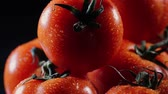tomate : A lot of ripe fresh tomato lying on a black glass table and rotates around its axis. Close-up fresh vegetables. Vídeos