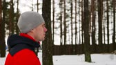 spurt : A young sporty man in a red jacket spends his training in the fresh air running along the pine forest in winter. Slow motion. 120 frames per second