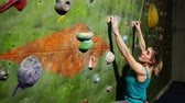 urvat : A female boulder trains to overcome obstacles on the wall for climbers. Professional rescuer. Climbing Wall