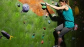 hüner : A female boulder trains to overcome obstacles on the wall for climbers. Professional rescuer. Climbing Wall. Slow motion