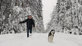 sibiř : In the winter forest, a man in a black jacket and jeans runs with a Siberian husky dog, a slow-motion shot. Pine fir forest, a merry walk with a dog. Slow motion