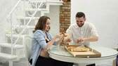 adiposidade : Man and pregnant woman eating pizza at home in their kitchen. Fatty foods Stock Footage