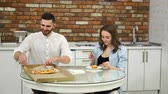 adiposidade : Man and pregnant woman eating pizza at home in their kitchen. Poor diet. Fatty foods. Obesity