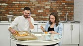 adiposidade : Man and pregnant woman eating pizza at home in their kitchen. Man talking on the phone during dinner Stock Footage